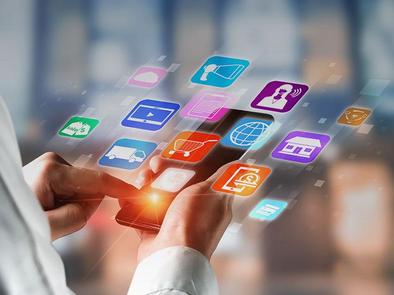 Une main tenant un smartphone avec les pictos des application qui sortent de l'écran